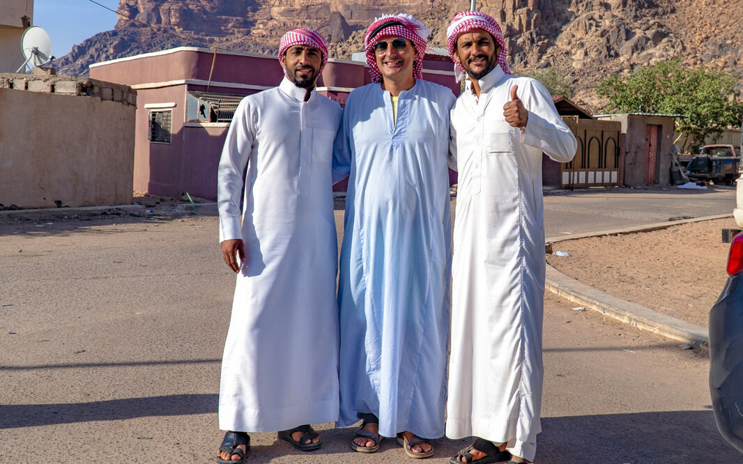 The Word Loves Americans. In the desert in Wadi Rum, Jordan, my 2 bedouin guides stand in white with me in the middle in blue.